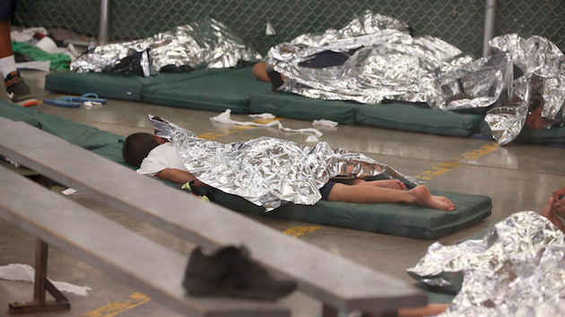 MIgrant children huddle under mylar blankets in the hielera. Photo: Ross D. Franklin/AP