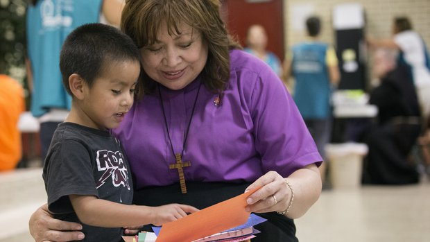 Bishop Minerva G. Carcaño, of the California-Pacific Conference of the United Methodist Church, with a young JFON client.