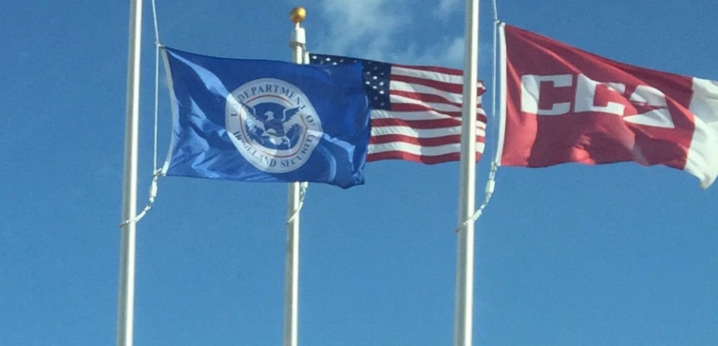 The flag of CCA—the for-profit prison corporation— flies next to the flag of the Department of Homeland Security and the flag of the United States of America.