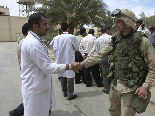 Iraqi and American soldier shake hands. Courtesy of city.data.com.